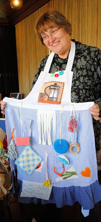Elke Röscher, Initiatorin des Näh- und Kreativ-Cafés, präsentiert eine der ehrenamtlich gefertigten Nestel-Schürzen, die für Menschen mit Demenz geeignet ist. Foto: Rinke